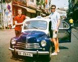 Two tall people standing next to a tiny taxi. With Tom Eaton in Ho Chi Minh City.